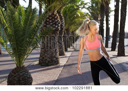 Charming female jogger stretching leg muscle while standing in palm park on running road
