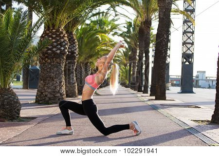 Athletic female with perfect body in sportswear do warm up exercise before morning run outdoors