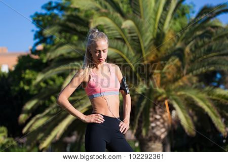 Fit woman with beautiful figure resting after active physical exercise outdoors in park