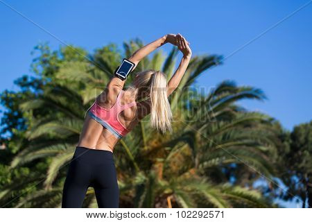 Fit caucasian woman witn perfect body working out in palm trees park outside