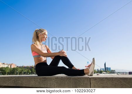 Young charming sports woman enjoys resting after workout outdoors