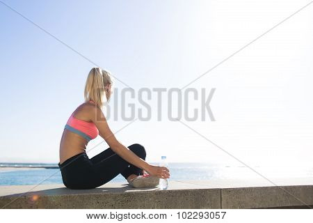 Female runner relaxing after morning run in the fresh air