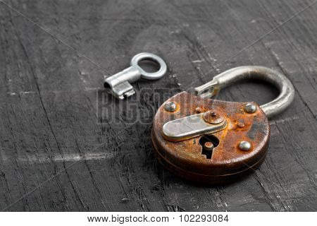 Open Antique Padlock With Key On Black