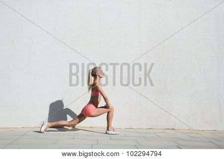 Fit woman warming up before running outdoors in summer day