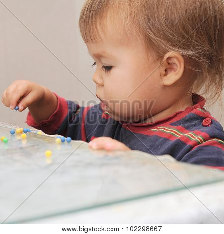 Little Baby Playing With Colored Pills
