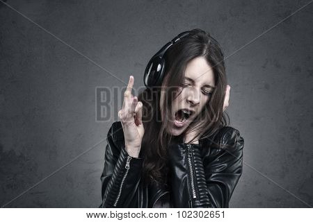 Young Woman With Head Phones Listening To Music And Singing