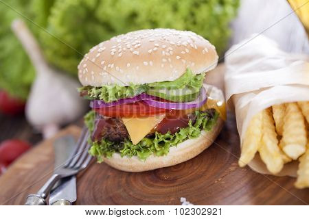 Beef Burgers On A Wooden Board With Chips And Aromatic Spices.