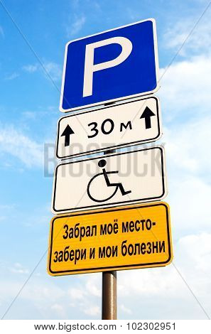 Handicapped Parking Sign Against Blue Sky. Text In Russian: Took My Place - And Take Away My Disease