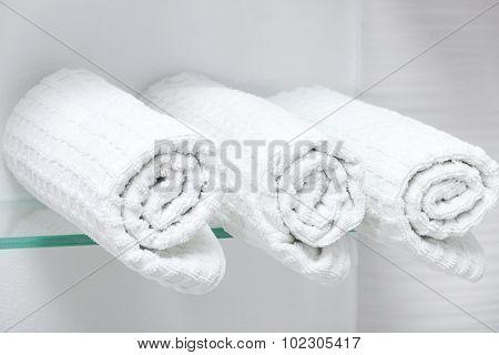 three white towel on a glass shelf
