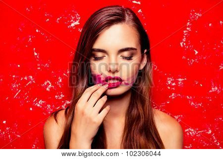 Sexy Model On A Red Background Rubbing Lipstick And Closing Eyes