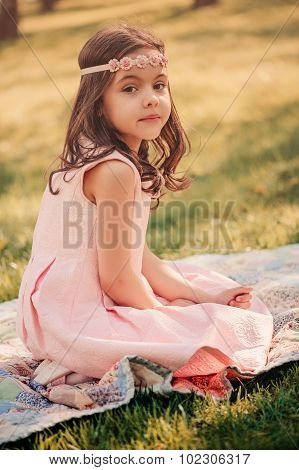 adorable child girl in pink dress and flower headband resting on blanket in summer park