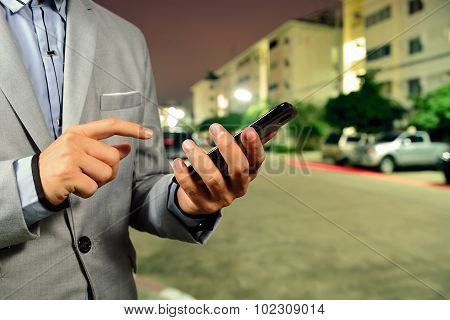 Young Businessman Use Mobile Phone In The Street