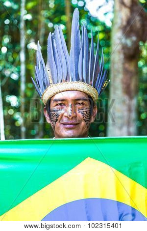 Native Brazilian man holding the Brazilian flag in the jungle in Amazon