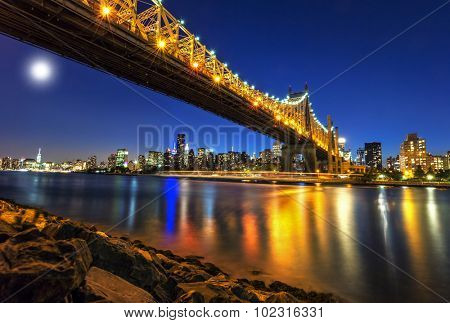 Queensboro Bridge over New York City East River with full moon