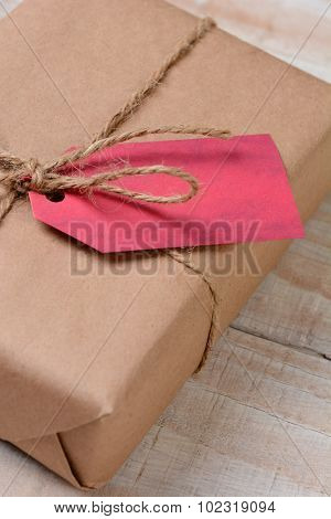 Closeup of an eco friendly christmas present - wrapped in recyclable plain brown paper and tied with twine. Vertical format on a rustic wood table. Shallow depth of field with copy space.
