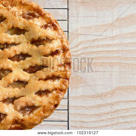High angle view of a fresh baked holiday apple pie on a cooling rack atop a rustic wood kitchen table. Only half the pie is shown leaving copy space.