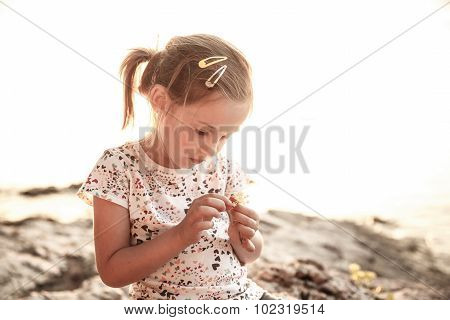 Little Girl Sitting On A Sunlit Beach At Sunset, Playing