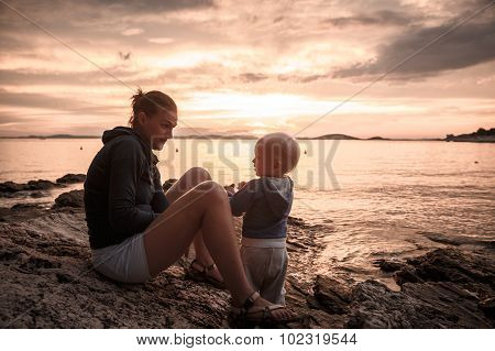 Mother And Son Sitting On A Rocky Beach, Talking And Playing