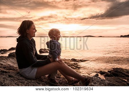 Mother And Son Sitting On A Rocky Beach, Having Fun