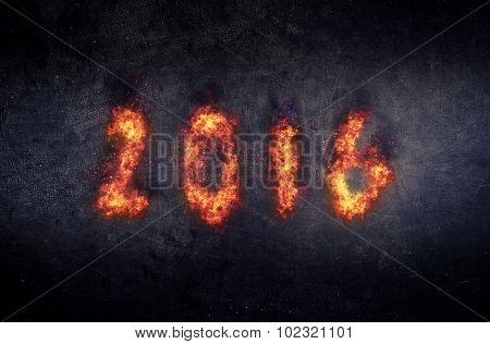 Flaming 2016 New Year background or greeting with fiery orange blazing numerals over a dark textured background with copyspace