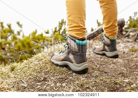 Back view close up of woman wearing yellow pants and hiking boots outdoors - adventure concept