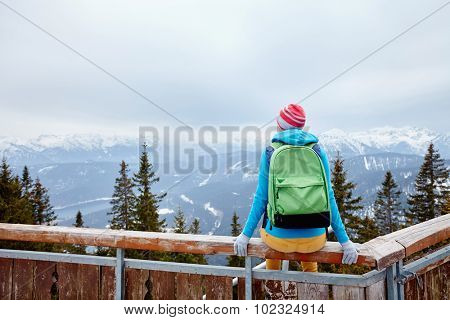 Back view of young woman wearing pink hat, blue jacket, green backpack and yellow pants sitting on wooden fence against winter mountain valley - adventure concept