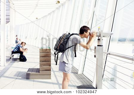 Young man with backpack looking through coin operated binoculars near window in airport