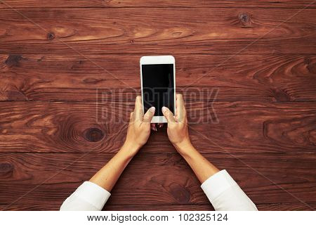 view from above on womans hands typing on smartphone over wooden brown table