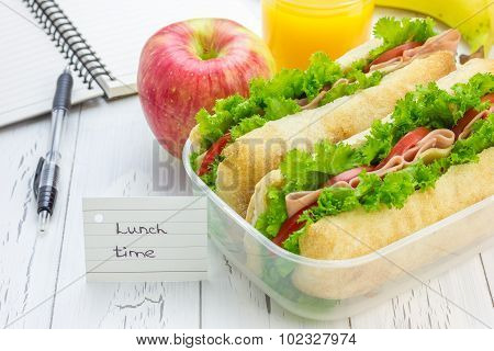 Lunch Box With Ciabatta Bread Sandwiches, Apple And Orange Juice On Workplace
