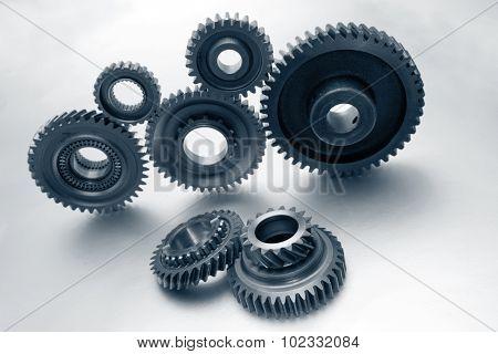 Seven steel cog wheels on plain background