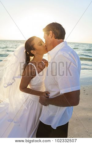 A married couple, bride and groom, kissing sunset sunrise on a beautiful tropical beach