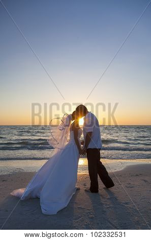 A married couple, bride and groom, kissing at sunset sunrise wedding on a beautiful tropical beach