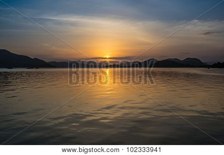 Wonderful sunset over the ocean, where sailing boat