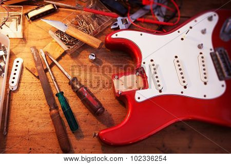 Red electric guitar body on guitar repair desk or in a repair work shop. Neck and pickguard detached. Double cutaway solid body guitar, red metallic color. Shallow depth of field.
