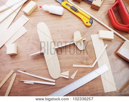 Handcrafting model airplane from wood. Wooden air plane handcrafted with balsa wood, on work table by the window. Airplane, cutter knife, balsa wood material and glue on table. Top view.