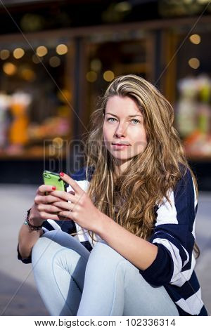 Confident woman, looking very casual sitting in the street, staring to the camera while sending text messages with her smart phone
