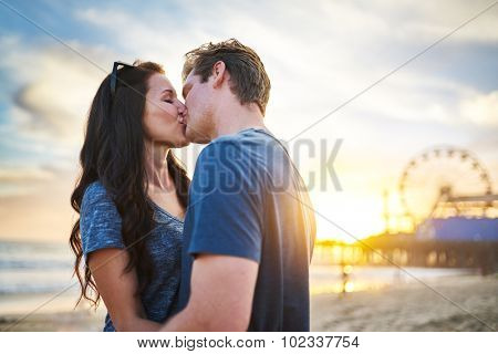 romantic couple kissing on beach in santa monica california at sunset.