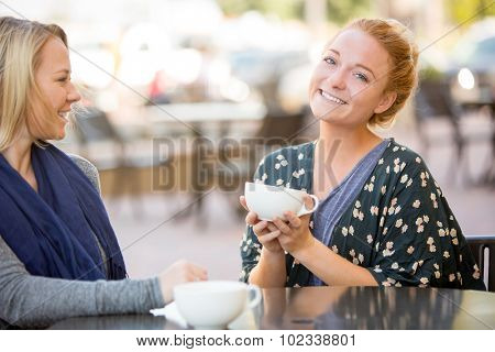 Two girlfriends getting coffee together outside