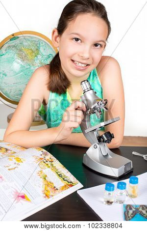 Little girl looking through microscope studying