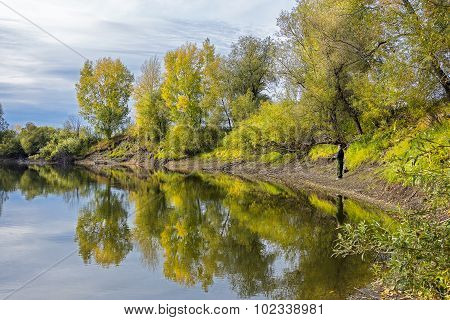 Autumn landscape on the river with fishermen