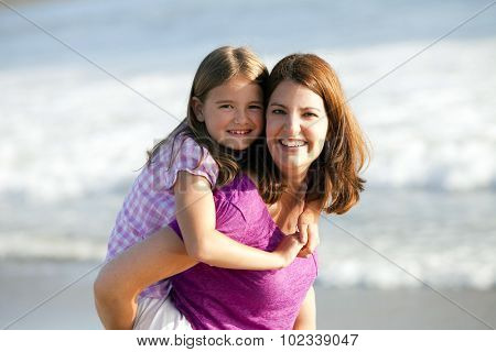 Loving mother and daughter playing on the beach