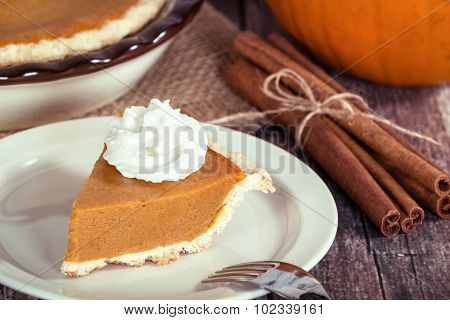 Slice Of A Pumpkin Pie On Wooden Table