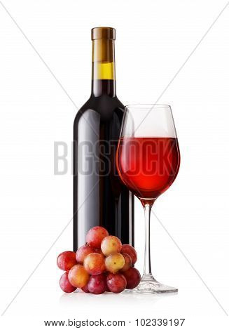 Glass and bottle of red wine with grapes