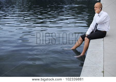 Businessman sitting on wall by lake, using mobile phone