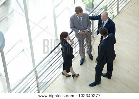 Businessmen and woman standing together by railing conversing