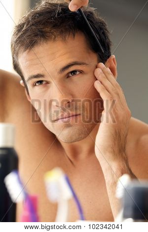 Young man combing his hair