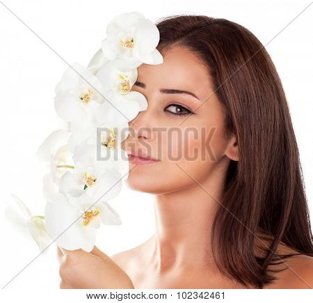 Portrait of beautiful woman with fresh orchid flowers on half of face isolated on white background, aroma therapy, enjoying day in luxury spa salon