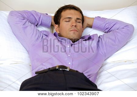 Man relaxing in hotel room with hands behind head, eyes closed