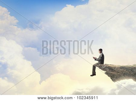 Young businessman sitting on rock edge with mobile phone in hand