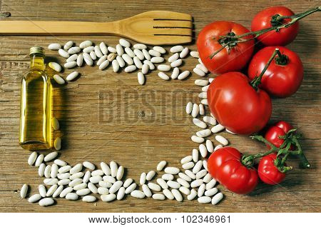 high-angle shot of a wooden fork, a bottle of olive oil, some white beans and some tomatoes on a rustic wooden table arranged to leave a blank space in the middle